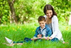 Mother and son with book in park. Mother and son with book sitting on green grass in park. Concept of happy family relations and carefree leisure time Stock Photo