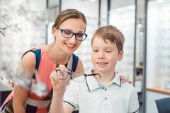 Mother and son both liking the eyeglasses offered in optician shop Royalty Free Stock Images