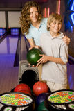 Mother and son in a bowling alley, holding green bowling ball Royalty Free Stock Image