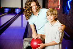 Mother and son in a bowling alley, holding red bowling ball Stock Images