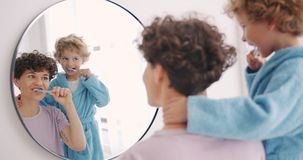 Mother and son brushing teeth in bathroom looking at mirror smiling together. Mother and son happy young people are brushing teeth in bathroom looking at mirror stock video footage