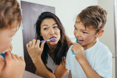 Mother and son brushing teeth in bathroom Stock Images