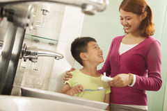 Mother and Son Brushing Teeth Together Stock Photos