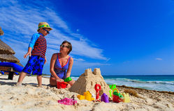 Mother and son building sand castle on tropical Royalty Free Stock Photos
