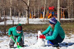 Mother and son building snowman in winter Royalty Free Stock Image