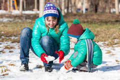Mother and son building snowman in winter Stock Image