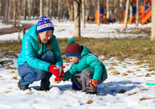 Mother and son building snowman in winter Royalty Free Stock Photo