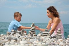 Mother and son builds stone stacks on beach Royalty Free Stock Photo