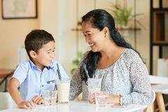 Mother and son in cafe. Cheerful Vietnamese women and her son enjoying milkshake in cafe royalty free stock photos