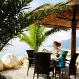 Mother and son in cafe. Young mother and baby son sit at table in sea beach cafe or bar under sun umbrella and palms on beautiful seascape Stock Images
