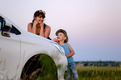 Mother and Son with Car in Field at Sunset Royalty Free Stock Photography