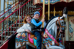 Mother and son on carousel Stock Photos