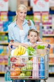 Mother and son with cart full of products in shopping mall Royalty Free Stock Photos
