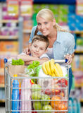 Mother and son with cart full of products in store Stock Photo