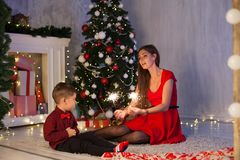 Mother and son celebrate the new year at a Christmas tree with gifts Garland lights stock images