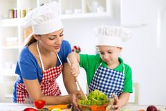 Mother and son with chef's cap prepare lettuce in kitchen Royalty Free Stock Images