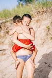 Mother and son child boy playing hugging on sand beach near sea ocean Royalty Free Stock Photography