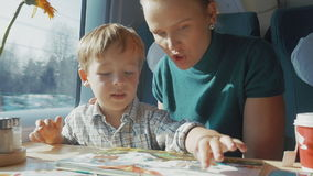 Mother and son with childrens book in the train stock video