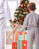 Mother and son and christmas gifts. Mother and son both in pyjama holding toy bunny looking at tree and christmas gifts in morning Stock Photo