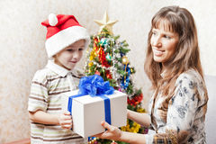 Mother and son with christmas holiday gift box. Smiling mother giving new year present or christmas holiday gift box to little son wearing Santa Claus hat Royalty Free Stock Photos