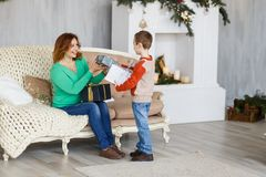 A mother and a son with christmas presents in front of the fur-tree with candles. Royalty Free Stock Photo