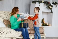 A mother and a son with christmas presents in front of the fur-tree with candles. Royalty Free Stock Images