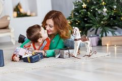 A mother and a son with christmas presents in front of the fur-tree with candles. stock images