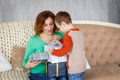 A mother and a son with christmas presents in front of the fur-tree with candles. Stock Photos