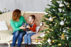 A mother and a son with christmas presents in front of the fur-tree with candles. Stock Image