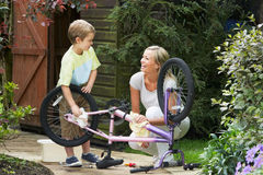 Mother And Son Cleaning Bike Together Stock Photos