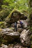 Mother and son climbing in a canyon Stock Photos