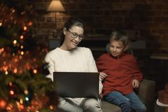 Mother and son connecting with a laptop at Christmas royalty free stock images