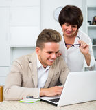 Mother and son consider software on laptop. Mother and son consider new software on laptop sitting at table Royalty Free Stock Images