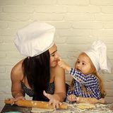 Mother and son cook together. Kid painting with flour on girl nose. Child and women in chef hats on white brick wall. Mothers day and happy childhood concept royalty free stock photography