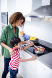 Mother and son cooking in kitchen. At home Stock Photos