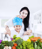 Mother and son cooking vegetable salad Royalty Free Stock Image
