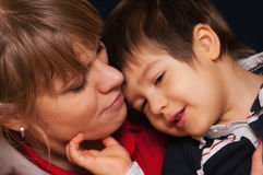 Mother and son cuddled up. Portrait of pretty young mother with her face touching  that of her son both looking happy and contented Stock Photo
