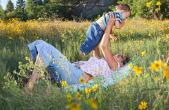Mother and son cuddling in late afternoon sun Stock Images