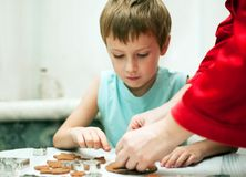 Mother and son cutting dough for christmas cookies. Mother teaching her son to cut dough for christmas cookies Stock Photo