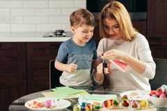 Mother and son cutting out paper with scissors at home, preparing Easter decor. stock photography