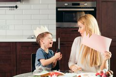 Mother and son cutting out paper with scissors at home, preparing Easter decor. Funny to prepare to Holy Easter with children. Attractive blonde women is stock image
