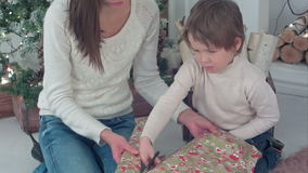 Mother and son cutting wrapping paper for Christmas gifts stock footage