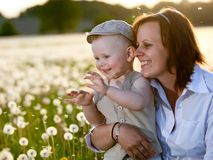 Mother and son with dandelions in meadow Royalty Free Stock Image
