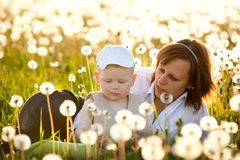Mother and son with dandelions in meadow Stock Images