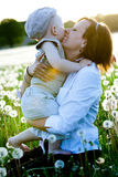 Mother and son with dandelions in meadow Stock Image