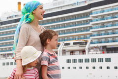 Mother, son and daughter in dock, looking right. Big cruise ship on background Royalty Free Stock Photo