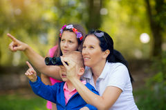 Mother and son and daughter exploring the environment with a binocular Stock Images