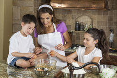 Mother Son Daughter Family Baking In A Kitchen. An attractive smiling family of mother, two children, girl, boy, son & daughter, breaking eggs & baking in a royalty free stock image