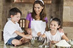 Mother Son Daughter Family Baking In A Kitchen. An attractive smiling family of mother and two children, girl boy, son daughter, baking in a kitchen at home royalty free stock photos