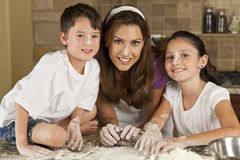 Mother Son & Daughter Family In Kitchen Baking. An attractive smiling mother, son and daughter family cooking and baking with flour and a rolling pin in a royalty free stock photos